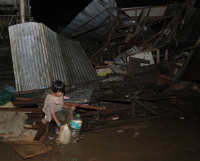 206421-a-boy-fetches-water-from-a-broken-pipe-among-destroyed-houses-along-a-